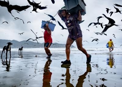ECUADORIAN FISHERMEN CARRYING BASKETS FULL OF FISH