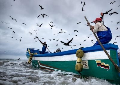ECUADORIAN FISHERMEN KEEPING THE BOAT STABLE