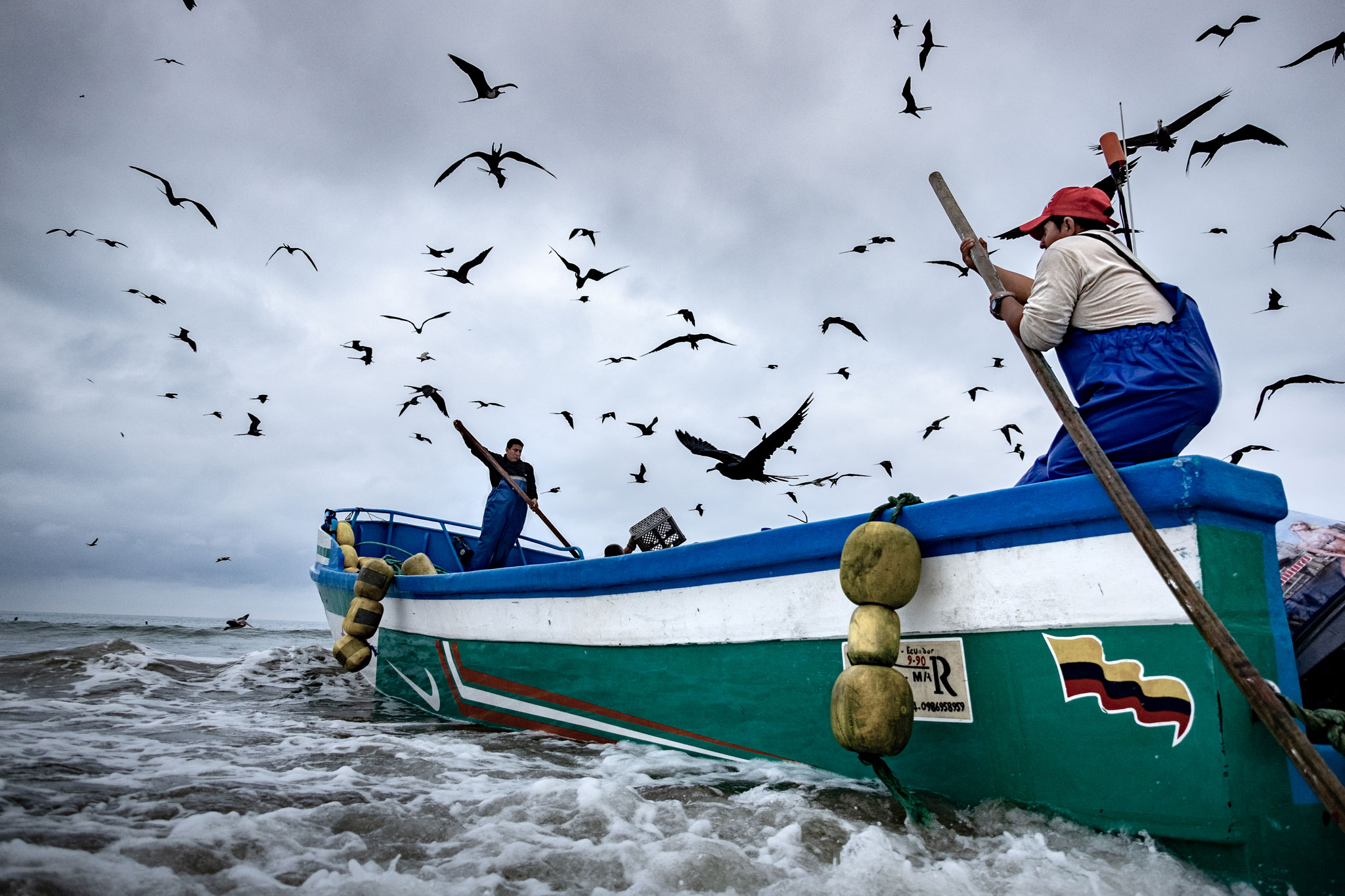 ECUADORIAN FISHERMEN KEEPING THE BOAT STABLE